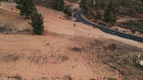 Εναέριος πυροβολισμός Οι ποδηλάτες κατεβαίνουν από το βουνό στα ποδήλατα βουνών με υψηλή ταχύτητα Στα πλαίσια των πράσινων δέντρω απόθεμα βίντεο