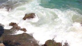 Εναέριο τοπ σπάσιμο κυμάτων άποψης στους σκοτεινούς βράχους κοντά στην παραλία απόθεμα βίντεο