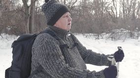 Ενεργός μια ηλικιωμένη γυναίκα συμμετείχε στο σκανδιναβικό περπάτημα με τα ραβδιά στην έννοια χειμερινού δασική υγιή τρόπου ζωής  φιλμ μικρού μήκους