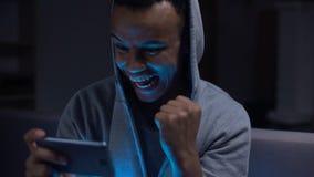 Εξαιρετικά συναισθηματικός μαύρος τύπος που κερδίζει το τηλεοπτικό παιχνίδι στο smartphone, απόθεμα βίντεο