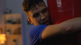 Εξαντλημένος έφηβος που αγκαλιάζει punching την τσάντα μετά από το εντατικό workout, ικανότητα, αθλητισμός φιλμ μικρού μήκους