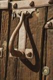 Εξολκέας και άρθρωση σιδήρου με τα στηρίγματα σε μια παλαιά ξύλινη πόρτα σε Caceres στοκ εικόνα