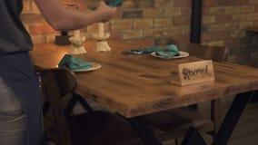 Εξυπηρετώντας πίνακας γευμάτων σερβιτορών με το διατηρημένο σημάδι για τη ρομαντική ημερομηνία Σερβιτόρα που προετοιμάζει το διατ απόθεμα βίντεο