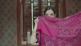 Εξωτική ντροπαλή ινδική γυναίκα που καλύπτει το πρόσωπο με τη Sari απόθεμα βίντεο