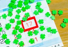 Εορταστικό υπόβαθρο ημέρας του ST Πάτρικ ` s Πράσινα quatrefoils επάνω από το ημερολόγιο με την πλαισιωμένη ημερομηνία στις 17 Μα στοκ εικόνες