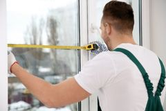 Εργάτης οικοδομών που μετρά το πλαστικό παράθυρο Επαγγελματική εγκατάσταση στοκ φωτογραφίες με δικαίωμα ελεύθερης χρήσης