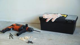 Εργαλεία εργασίας - ηλεκτρικό τρυπάνι, επίπεδο λέιζερ, κιβώτιο με τα όργανα και τα γάντια απόθεμα βίντεο