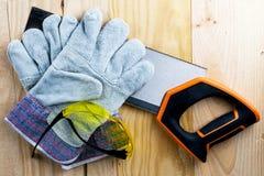 Εργασία για την κατασκευή ή την επισκευή του σπιτιού ανακαίνιση Η εργασία πριονιών χρήσης φορά γάντια στο μέτρο ταινιών Ασφάλεια  στοκ φωτογραφίες