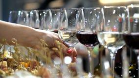 Εύγευστος πίνακας μπουφέδων Το θηλυκό χέρι παίρνει ένα ποτήρι του άσπρου κρασιού 4K αργό MO φιλμ μικρού μήκους