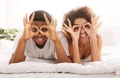 Εύθυμα ευτυχή δάχτυλα εκμετάλλευσης ζευγών ερωτευμένα κοντά στα μάτια στοκ εικόνα