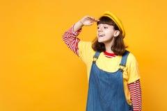 Εύθυμος έφηβος κοριτσιών γαλλικό beret, χέρι εκμετάλλευσης τζιν sundress στο μέτωπο που φαίνεται μακριά απόσταση που απομονώνεται στοκ φωτογραφία