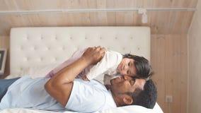 Εύθυμος πατέρας που ανυψώνει λίγη κόρη επάνω στο κρεβάτι απόθεμα βίντεο