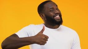 Εύθυμο άτομο αφροαμερικάνων που παρουσιάζει αντίχειρες που απομονώνονται επάνω στο κίτρινο υπόβαθρο φιλμ μικρού μήκους