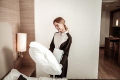 Εύθυμο κορίτσι ξενοδοχείων που κρατά το μεγάλο comfy άσπρο μαξιλάρι στοκ εικόνες με δικαίωμα ελεύθερης χρήσης