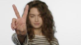 Εύθυμο κορίτσι που παρουσιάζει χέρι σημαδιών β Πορτρέτο της γυναίκας που παρουσιάζει χειρονομία νίκης απόθεμα βίντεο