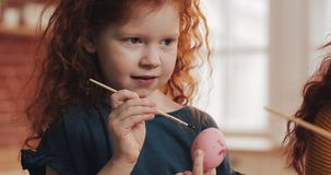 Εύθυμο redhead κορίτσι παιδάκι με τη μητέρα της που χρωματίζει το αυγό Πάσχας στο υπόβαθρο κουζινών Πάσχα ευτυχές στοκ εικόνες