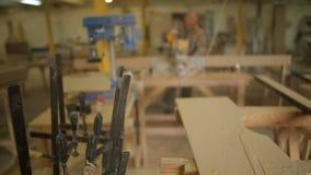 Εστίαση στους φ-σφιγκτήρες ή τους σφιγκτήρες φραγμών και εργασίες ξυλουργών ή ξυλουργών στο εργαστήριο των επίπλων στο υπόβαθρο φιλμ μικρού μήκους