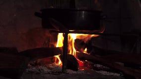 Εσωτερική ξύλινη πυρκαγιά στην παραδοσιακή κουζίνα με το τηγάνι απόθεμα βίντεο