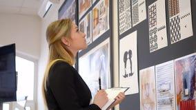 Εσωτερικός σχεδιαστής γυναικών που εργάζεται με το δημιουργικό σχεδιάγραμμα στο επιχειρησιακό γραφείο απόθεμα βίντεο