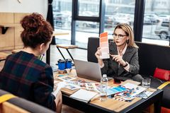 Εσωτερικός σχεδιαστής που φορά τα γυαλιά που ρωτούν τις συμβουλές του χρήσιμου βοηθού της στοκ φωτογραφία με δικαίωμα ελεύθερης χρήσης