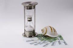 ΕΥΡΟ- τραπεζογραμμάτια, κλεψύδρα και θαλασσινό κοχύλι στο άσπρο υπόβαθρο Έννοια - χρόνος να ταξιδεψει στοκ φωτογραφία με δικαίωμα ελεύθερης χρήσης