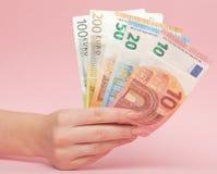 Ευρο- χρήματα τραπεζογραμματίων στα θηλυκά χέρια στο ρόδινο υπόβαθρο Επιχειρησιακά έννοια και Instagram στοκ εικόνες