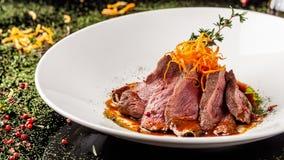 Ευρωπαϊκή κουζίνα Μαριναρισμένο μοσχαρίσιο κρέας με το μέσο ψητού σπάνιο Βαθμός ψησίματος Ο αρχιμάγειρας χύνει το ελαιόλαδο βόειο στοκ εικόνα με δικαίωμα ελεύθερης χρήσης