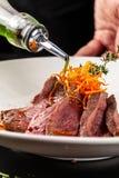 Ευρωπαϊκή κουζίνα Μαριναρισμένο μοσχαρίσιο κρέας με το μέσο ψητού σπάνιο Βαθμός ψησίματος Ο αρχιμάγειρας χύνει το ελαιόλαδο βόειο στοκ εικόνες