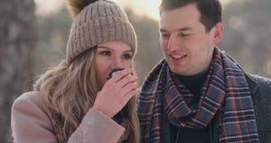 Ευτυχές ζεύγος που κρατά τα καυτά φλυτζάνια τσαγιού πέρα από το χειμερινό τοπίο Νέο ζεύγος ερωτευμένο σε χειμερινές διακοπές, που απόθεμα βίντεο