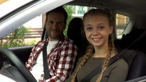 Ευτυχές θηλυκό χαμόγελο στη κάμερα, καθμένος στο αυτοκίνητο με τον εκπαιδευτικό, οδηγώντας σχολείο στοκ εικόνες