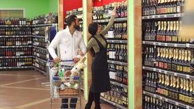 Ευτυχές μοντέρνο ζεύγος που επιλέγει το κρασί μαζί περπατώντας στο κατάστημα κρασιού απόθεμα βίντεο