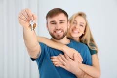 Ευτυχές νέο ζεύγος με το κλειδί από το καινούργιο σπίτι τους στοκ φωτογραφία