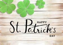 Ευτυχές του ST Πάτρικ υπόβαθρο τυπογραφίας κειμένων ημέρας μαύρο με τα πράσινα τριφύλλια στην ξύλινη σύσταση στοκ φωτογραφία με δικαίωμα ελεύθερης χρήσης