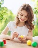 Ευτυχές χαμογελώντας κορίτσι που χρωματίζει τα αυγά Πάσχας στοκ φωτογραφία