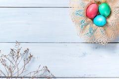 Ευτυχές υπόβαθρο συνόρων Πάσχας, πλαίσιο των ζωηρόχρωμων αυγών Πάσχας στο καλάθι και κλάδος των ξηρών λουλουδιών στοκ εικόνες με δικαίωμα ελεύθερης χρήσης