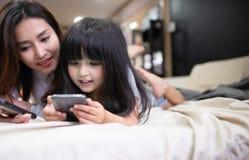 Ευτυχές smartphone παιχνιδιού κορών πορτρέτου με τη μητέρα της στοκ εικόνες με δικαίωμα ελεύθερης χρήσης