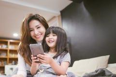 Ευτυχές smartphone παιχνιδιού κορών πορτρέτου με τη μητέρα της στοκ εικόνα