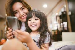 Ευτυχές smartphone παιχνιδιού κορών πορτρέτου με τη μητέρα της στοκ εικόνα με δικαίωμα ελεύθερης χρήσης