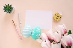 Ευτυχής έννοια Πάσχας με την κενή κάρτα και τις ζωηρόχρωμες τουλίπες αυγών Πάσχας ροζ και στοκ εικόνες