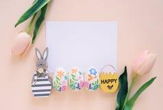 Ευτυχής έννοια Πάσχας με την κενή κάρτα, το ξύλινο λαγουδάκι, τα ζωηρόχρωμα αυγά Πάσχας και τις ρόδινες τουλίπες στοκ φωτογραφία με δικαίωμα ελεύθερης χρήσης