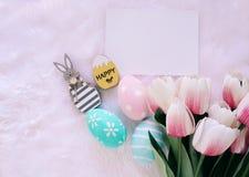 Ευτυχής έννοια Πάσχας με το ξύλινο λαγουδάκι και τα ζωηρόχρωμα αυγά Πάσχας στο άσπρο υπόβαθρο γουνών και τις ρόδινες τουλίπες στοκ εικόνα