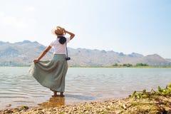 Ευτυχής ασιατική γυναίκα στον περιστασιακό ιματισμό ύφους που στέκεται στον ποταμό με τη θέα βουνού στοκ φωτογραφίες με δικαίωμα ελεύθερης χρήσης
