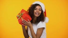 Ευτυχής γυναίκα αναμιγνύω-φυλών στο καπέλο santa που χορεύει με το κόκκινο giftbox στα χέρια, διακοπές φιλμ μικρού μήκους