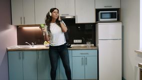 Ευτυχής γυναίκα που χορεύει και που ακούει τη μουσική με τα ακουστικά στην κουζίνα που μαγειρεύει και που τρώει το μήλο φιλμ μικρού μήκους
