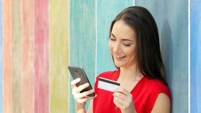 Ευτυχής γυναίκα που πληρώνει on-line σε έναν ζωηρόχρωμο τοίχο φιλμ μικρού μήκους