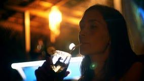 Ευτυχής ελκυστική νέα επιχειρηματίας που απολαμβάνει το τροπικό ποτό κοκτέιλ στο φραγμό σαλονιών παραλιών βραδιού στο θέρετρο δια απόθεμα βίντεο