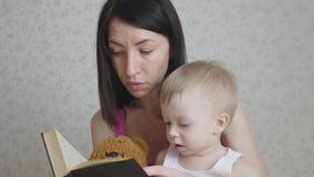 Ευτυχής μητέρα που διαβάζει ένα βιβλίο στο αγόρι παιδιών στο εσωτερικό Γλυκιά στιγμή με το βιβλίο ανάγνωσης μητέρων στο μωρό απόθεμα βίντεο