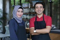 Ευτυχής νέος ασιατικός ιδιοκτήτης καφέδων ζευγών μπροστά από το χαμόγελο καφετεριών πορτρέτο δύο σερβιτόρων στο εστιατόριο στοκ φωτογραφίες