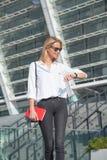 Ευτυχής ξανθή επιχειρησιακή γυναίκα στα γυαλιά ηλίου που ελέγχει το χρόνο με το ρολόι σε ετοιμότητα σε σχέση με σύγχρονου κτηρίου στοκ εικόνες