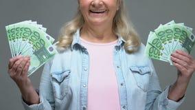Ευτυχής ώριμη γυναίκα που παρουσιάζει ευρο- τραπεζογραμμάτια, εύκολη πίστωση τραπεζών, συνταξιοδοτικός πλούτος απόθεμα βίντεο
